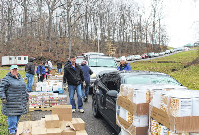 Indivisible Appalachian Ohio volunteers, along with a group from WOUB's Community Giveback Program, loaded vehicles during the food pantry.