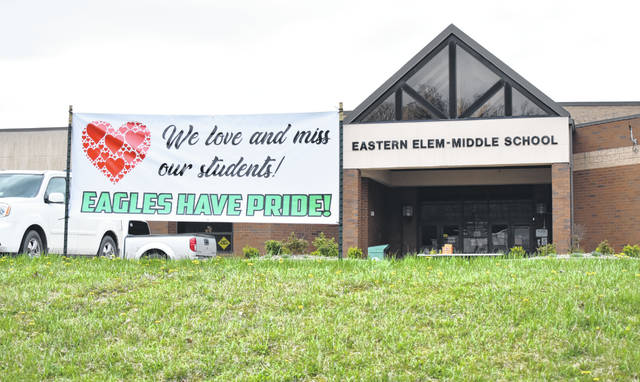 "A sign in front of Eastern Elementary and Middle School reads ""We love and miss our students. Eagles have pride."""