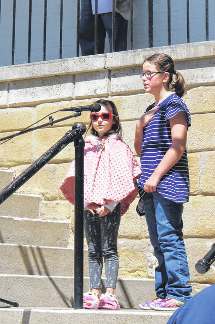 Lyla Beasley and Zoey Barnhart lead the pledge to the Christian Flag and Bible during the Meigs County National Day of Prayer event on Thursday.