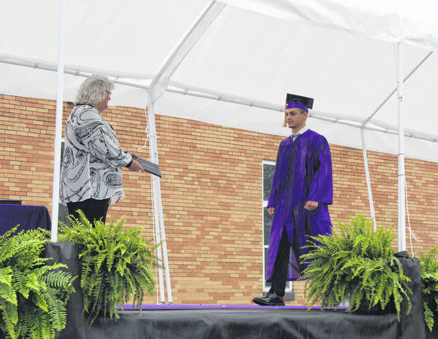 Gage Barrett walks across the stage to receive his diploma from Southern Local Board of Education President Brenda Johnson.