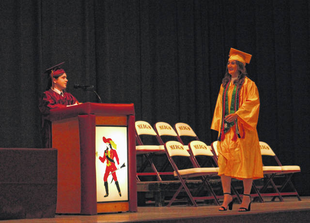 Annie McGrath walks across the stage to receive her diploma as Class Secretary Brian Ackley Jr. looks on.