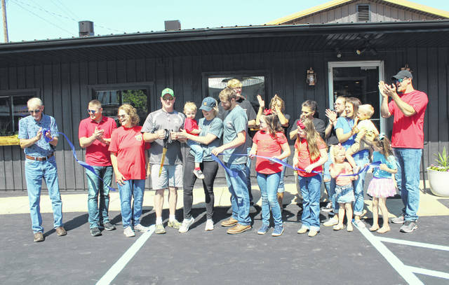 The grand reopening of Fox's Pizza Den in Rutland was celebrated on Tuesday with a ribbon cutting. Pictured are members of the Kernen and Stewart families, Fox's Rutland employees and Meigs County Commissioners.