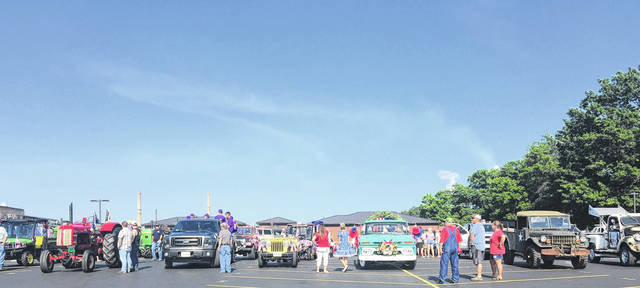Lines of vehicles prepare to leave the parking lot to begin the Independence Day parade.