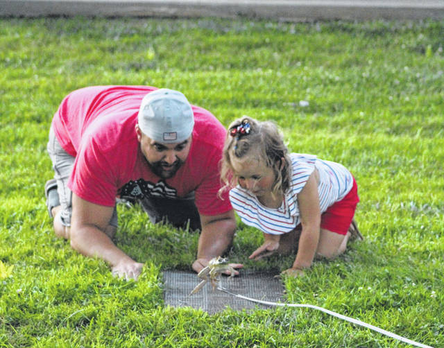 Wes Riffle and his daughter Emersyn take part in the Frog Jumping contest on Saturday at Racine's Star Mill Park.