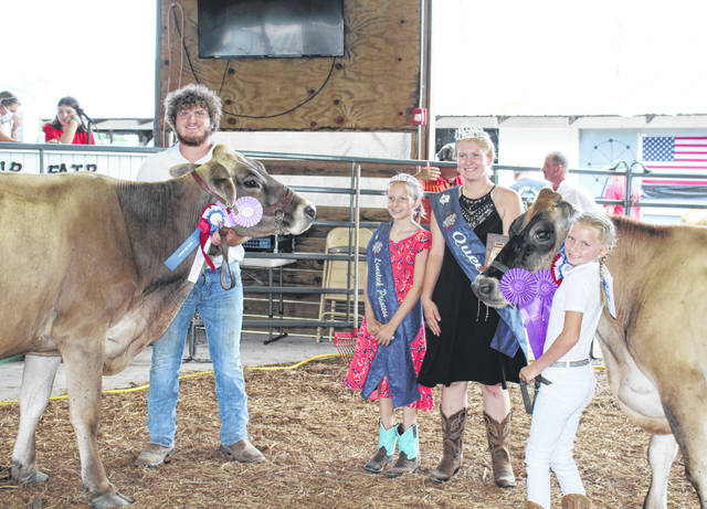 Coltin Parker's Brown Swiss was named Reserve Champion and Alyssa Richards' Jersey was named the Grand Champion during Monday's Dairy Show. Also pictured are Fair Queen Kristin McKay and Livestock Princess Nevada Johnson.