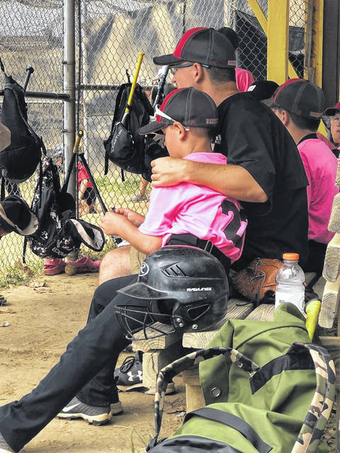 Coach Pat Martin puts an arm around his son, Jeremiah, in the dugout during a local baseball game.