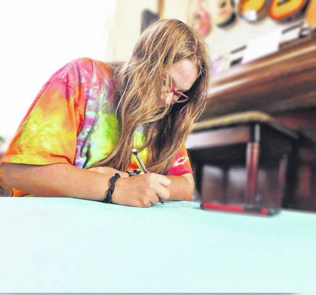 Pictured is local artist Halo Rife hard at work and wearing her design for a t-shirt from River Roaster's Coffee Company in Pomeroy. (Phoebe Rife | Courtesy)