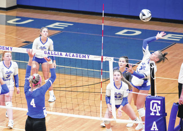 Gallia Academy sophomore Callie Wilson, right, leaps for a spike attempt during Thursday night's OVC volleyball contest against Portsmouth in Centenary, Ohio.