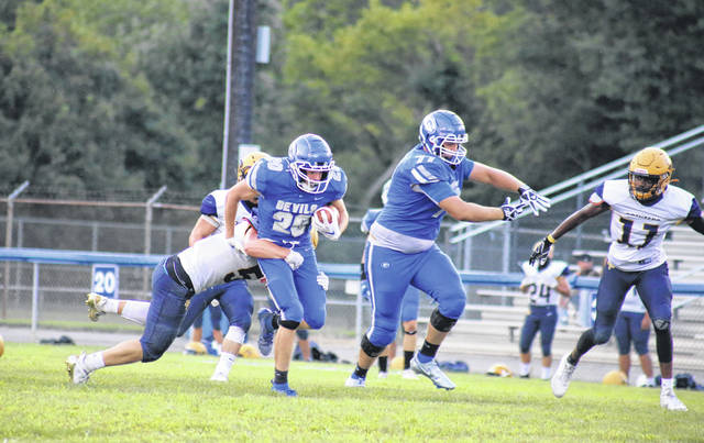 GAHS senior Michael Beasy (20) breaks a tackle, while sophomore Isaac Clary (77) blocks an incoming defender, during the Blue Devils' Week 1 win over South Point on Aug. 28 in Gallipolis, Ohio.