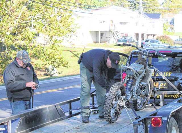 Sgt. Frank Stewart and Sheriff Keith Wood load the dirt bike onto a trailer to return it to the family.