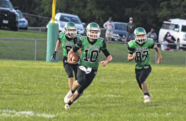 Eastern senior Conner Ridenour (10) carries the ball after an interception in front of teammates Bryce Newland (6) and Bruce Hawley (87), during the Eagles' 10-7 loss to Trimble on Sept. 4 in Tuppers Plains, Ohio.
