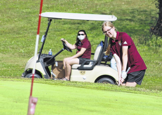 Meigs senior Caitlin Cotterill hits a chip shot as MHS coach Alyssa Andrews watches on in the background at the 2020 Division II Southeast Sectional golf tournament held at Franklin Valley Golf Course on Sept. 28 in Jackson, Ohio.