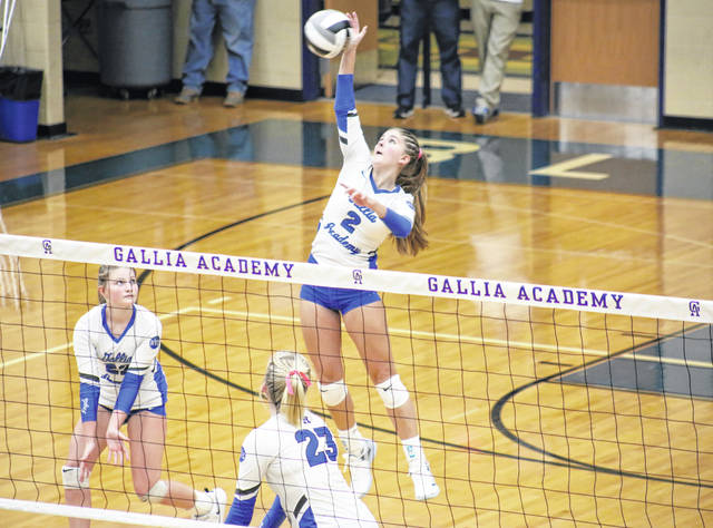 Gallia Academy junior Bailey Barnette (2) spikes the ball over the net after a set from Regan Wilcoxon (left), during the Blue Angels' sweep of Athens on Wednesday in Centenary, Ohio.