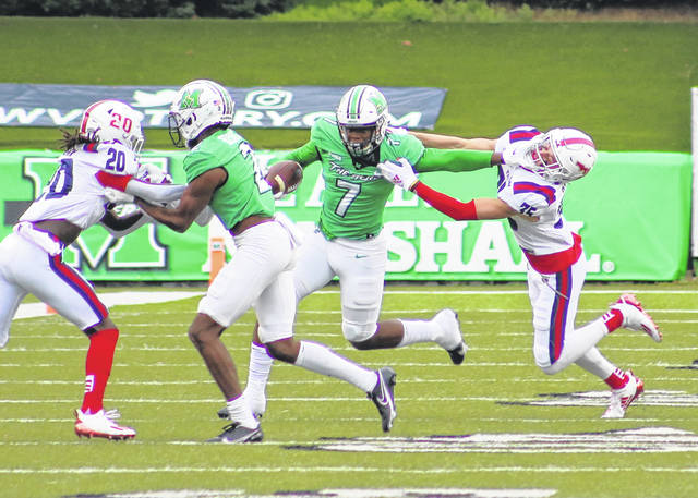 Marshall wideout Corey Gammage (7) delivers a stiff arm to a Florida Atlantic defender during the first half of Saturday's football game at Joan C. Edwards Stadium in Huntington, W.Va.