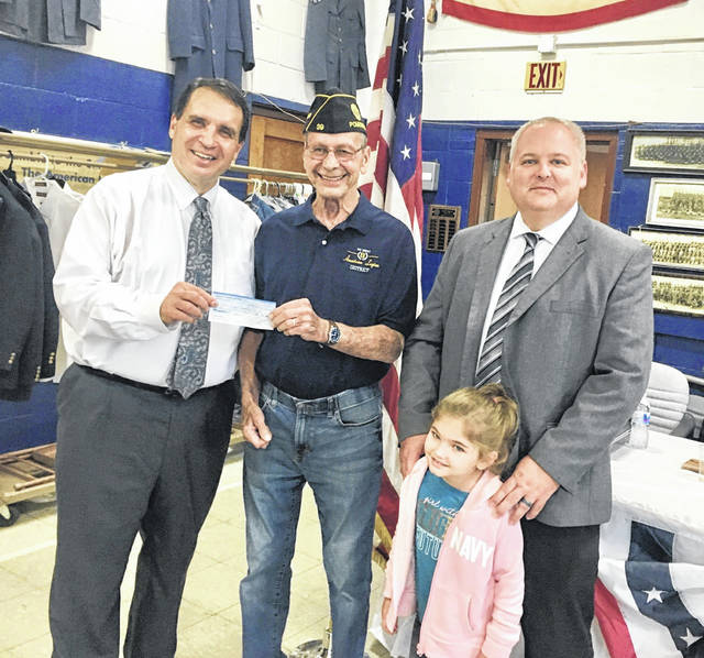 Attorney Adam Salisbury and his daughter, Hannah, look on as Attorney Chris Tenoglia presents Post 39 Legion Commander John Hood with a check in the amount of $2,500 to assist Veterans with travel costs.