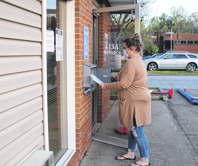 Meigs County Board of Elections Director Angie Robson removes a ballot from the drop box at the Meigs County Board of Elections during the 2020 Primary Election.