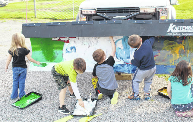 """Children at Munchkin City Daycare in Middleport recently spent an afternoon leaving their mark on one of the Village of Middleport's now plows. The village brought the plow to the daycare where children in the """"green"""" room, mostly ages 4 and 5, spent time painting different colors, shapes and designs on the plow. After a little finishing work by the staff, the plow was returned to the village to be used to clear the streets this winter. On Thursday, the village brought a second snow plow to the daycare for the kids to paint as well."""