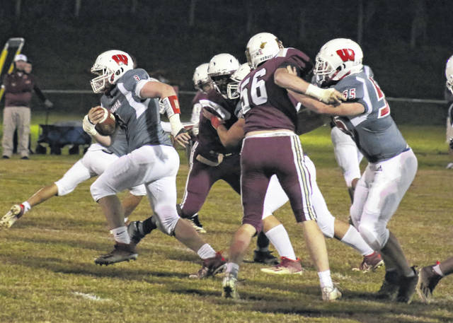 Wahama senior Brennan Grate, left, breaks through the line of scrimmage for additional yardage during the first half of Friday night's football game against Trinity Christian at Bachtel Stadium in Mason, W.Va.