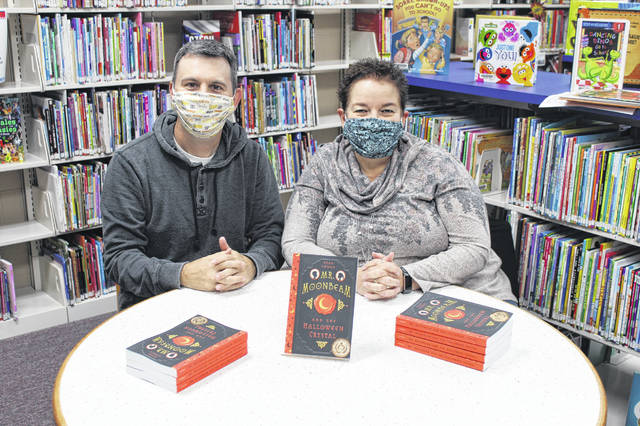Author Ryan Cowan and teacher Shelia Bevan are pictured with the books which were donated to the Middleport Library.