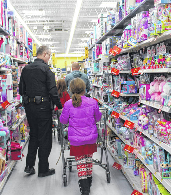 Pomeroy Police Chief Chris Pitchford helps a child shop during the 2019 Shop with a Cop event.