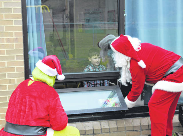 Santa, accompanied by the Grinch, took time out of his busy holiday schedule for a socially distanced visit on Friday afternoon at Carleton School. Santa and the Grinch made their rounds on the outside of the building, waiving to the students through the windows and even passing in a few presents which the Grinch tried to steal. Students were able to come to the window to talk with Santa and take a few photos.