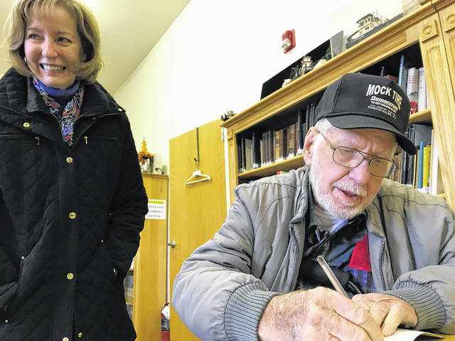 From 2017, William Edmondson of King, N.C., pictured sitting, signs a book for Gina Cocklereece of Winston-Salem, N.C. Edmondson was a survivor of the Silver Bridge collapse and was driving a tractor trailer on Dec. 15, 1967 along with Cocklereece's father, Harold Cundiff, who didn't survive. They both visited Point Pleasant for the 50th anniversary of the tragedy in 2017.