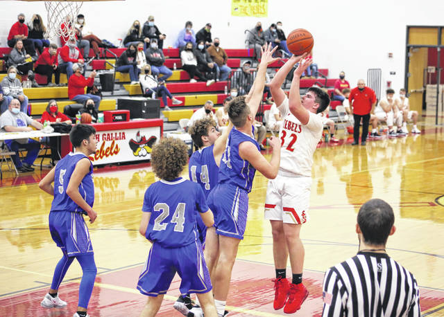South Gallia junior Ean Combs (32) releases a shot attempt over several Sciotoville East defenders during the first half of Tuesday night's boys basketball contest in Mercerville, Ohio.