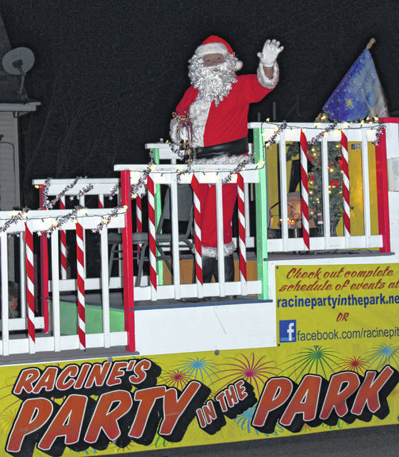 Santa waves to parade watchers from atop the Party in the Park float.