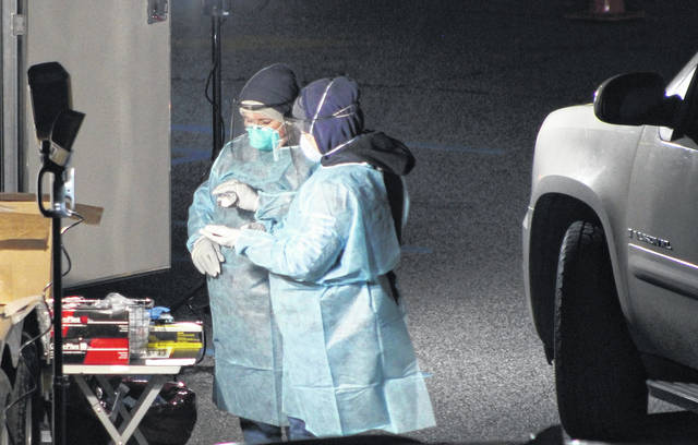 Staff from the Mason County Health Department bundle up against the cold and reach for the hand sanitizer during Monday evening's free COVID-19 testing in Point Pleasant, W.Va. Assisting at the drive-thru testing site were personnel with the Mason County Division of Homeland Security and Emergency Managment. (Beth Sergent | OVP)