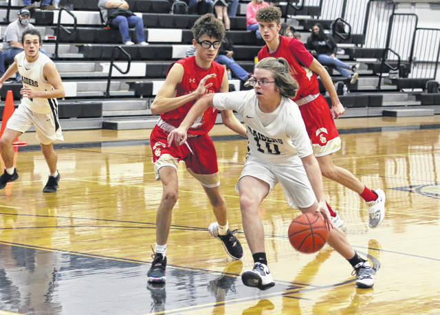 River Valley senior Chase Barber (10) dribbles past South Gallia defender Blaik Saunders during the second half of Tuesday night's boys basketball contest in Bidwell, Ohio.