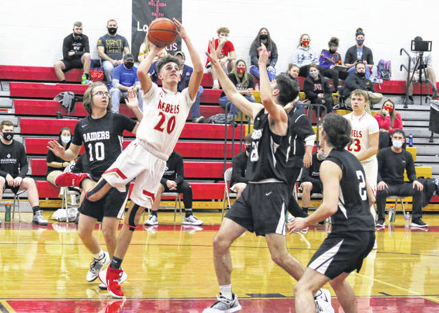 South Gallia junior Brayden Hammond (20) releases a shot attempt between a pair of River Valley defenders during the first half of Tuesday night's boys basketball contest in Mercerville, Ohio.