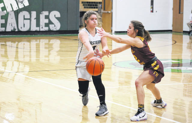 Eastern freshman Hope Reed (left) passes around Federal Hocking senior Paige Tolson (right), during the Lady Lancers' 64-52 victory on Thursday in Tuppers Plains, Ohio.