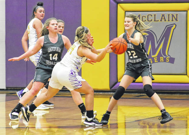 River Valley defenders Emma Truance (14) and Sierra Somerville (22) apply pressure to a McClain player during the first half of Friday night's Division II girls sectional final at McClain High School in Greenfield, Ohio.