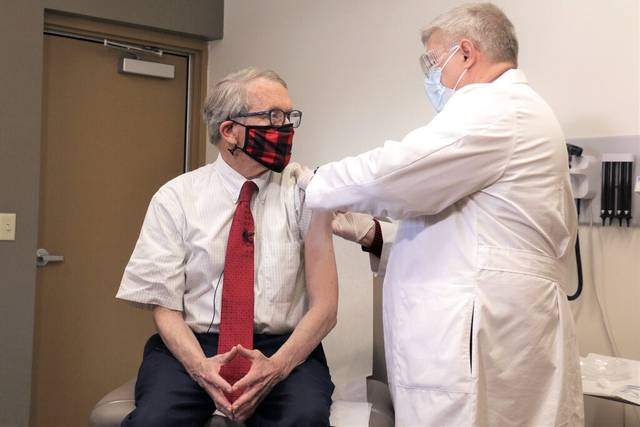 Ohio Gov. Mike DeWine, left, gets his first dose of the COVID-19 vaccine from Dr. Kevin Sharrett, Tuesday in Jamestown, Ohio. Dewine became eligible to receive his first shot this week as vaccinations are now open to Ohioans age 70 and above. (Ohio Governor's Office via AP)