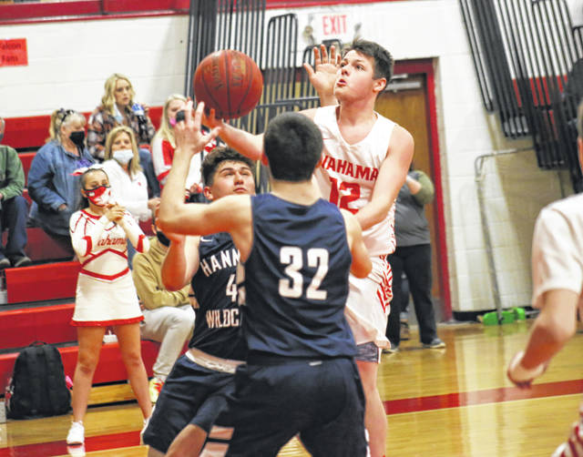 Wahama's Jace Ervin (12) goes in for a layup between Wildcats Xavier Stone (4) and Brady Edmunds (32), during the fourth quarter of the White Falcons' 87-30 victory on Saturday in Mason, W.Va.