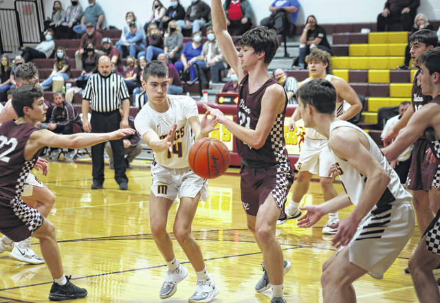 Meigs freshman Braylon Harrison (14) passes to senior Zach Searles in the low post, during the Marauders' three-point victory on Monday in Rocksprings, Ohio.