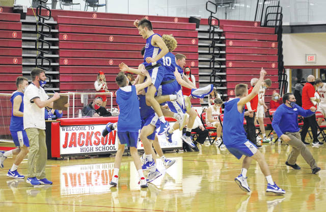 Members of the GAHS boys basketball team celebrate a 40-37 victory in the D-2 district semifinal on Thursday in Jackson, Ohio.