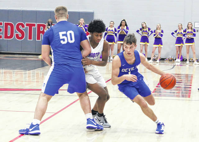 Gallia Academy senior Cooper Davis uses a screen by teammate Isaac Clary (50) to dribble past Unioto defender DeSean Branson during the second half of Saturday night's Division II Southeast 2 district championship game held at Piketon High School in Piketon, Ohio.