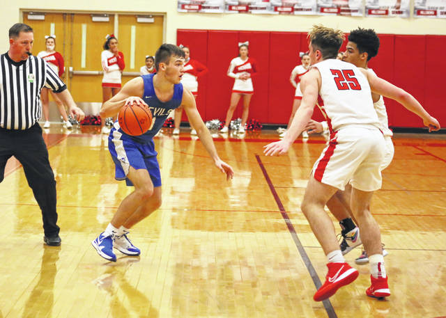 Gallia Academy senior Cooper Davis, left, dribbles away from a pair of Hillsboro defenders trying to trap him during the second half of a Division II sectional final matchup at Hillsboro High School on Feb. 25 in Hillsboro, Ohio.