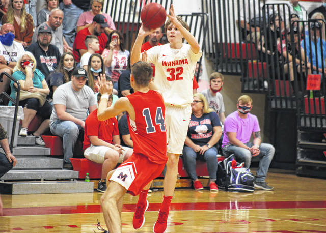 Wahama sophomore Ethan Gray (32) fires a three-pointer over Man junior Austin Ball (14), during the Class A Region IV co-final on Wednesday at Gary Clark Court in Mason, W.Va.