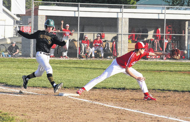 Eastern senior Brad Hawk (left) safely makes it to first, just before Wahama sophomore Ethan Gray (right) catches the ball, during the fourth inning of the Eagles' 10-4 win on Monday in Mason, W.Va.