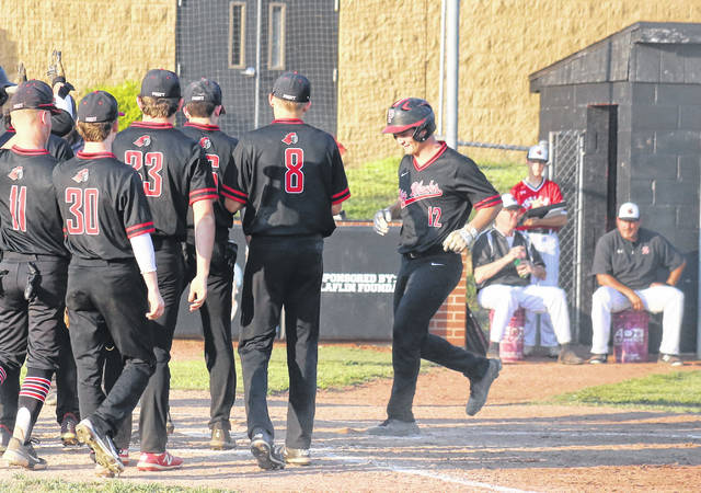 Point Pleasant senior Joel Beattie (12) is greeted by his teammates after a home run, during the Big Blacks' victory over Sissonville on Tuesday in Point Pleasant, W.Va.