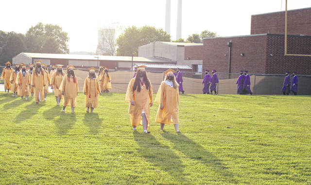 Graduates march across the football field for Sunday's commencement ceremony.