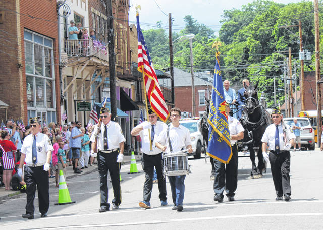 A drummer and local American Legion and VFW members march in front of the horse drawn hearse on Saturday afternoon.