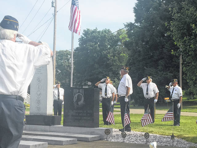 Members of American Legion Post 602 and Veterans of Foreign Wars Post 9053 salute the flag during Monday's flag raising ceremony. On Memorial Day morning, the flag is raised briskly, then lowered to half-staff to honor the fallen. At noon, the flag is raised to full staff until sunset.
