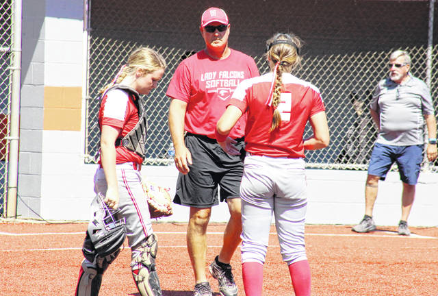Wahama head coach Chris Noble meets with pitcher Mikie Lieving (2) and catcher Amber Wolfe (left), during the Lady Falcons' 5-3 victory in the Class A state championship on Wednesday in South Charleston, W.Va.