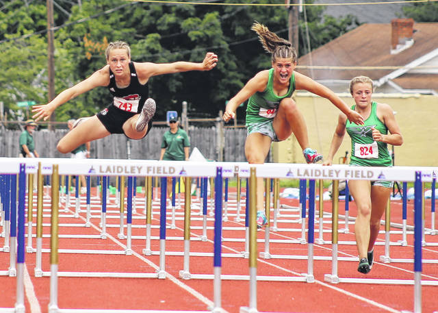 Point Pleasant junior Elicia Wood, left, clears an obstacle in the 100m hurdles final final on Friday at the Class AA track and field championships held at Laidley Field in Charleston, W.Va.