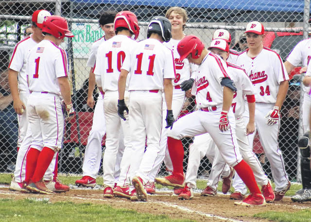 Wahama junior Ethyn Barnitz (4) is surrounded by teammates as he touches home plate after a home run in a regular season baseball game in Mason, W.Va.