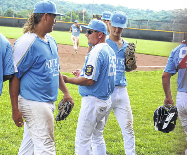 Post 39 head coach Bill Gilkey greets Andrew Dodson (left) and Matthew Blanchard (right) as they head into the dugout, during a June 13 victory in Rocksprings, Ohio.