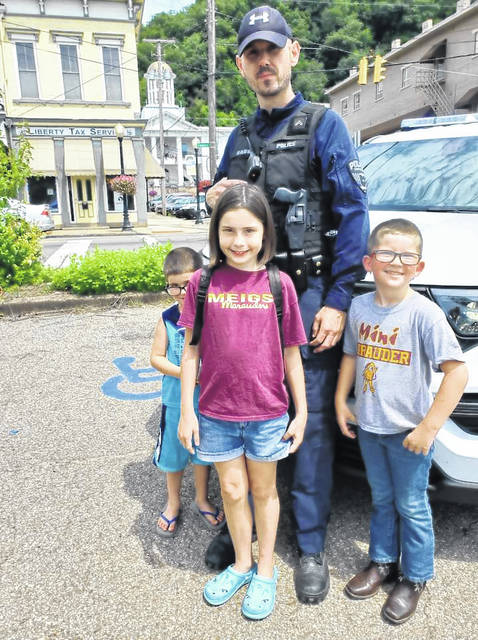 Pomeroy Police Officer Leif Babb is pictured with children at the Meigs County Farmers' Market.